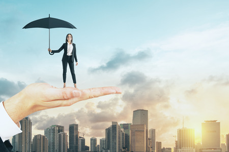 Big hand holding young woman with umbrella on bright city background with sunlight. Protection and success concept 写真素材
