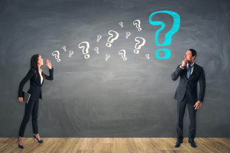 黒板の壁の背景についてお互いに質問するビジネスマンと女性。コミュニケーションと質問の概念 写真素材