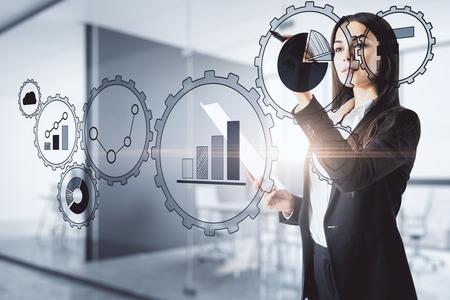 Attraktive junge europäische Geschäftsfrau, die digitale Zahnradgeschäftsschnittstelle auf undeutlichem Büroinnenhintergrund verwendet Spott oben. Zukunfts- und Technologiekonzept. Standard-Bild
