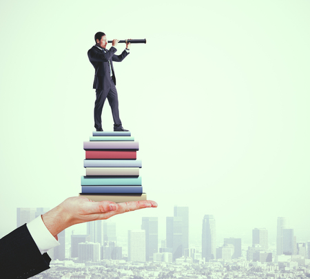 Attractive young european businessman using telescope while standing on pile of books on blurry city background. Knowledge and future concept