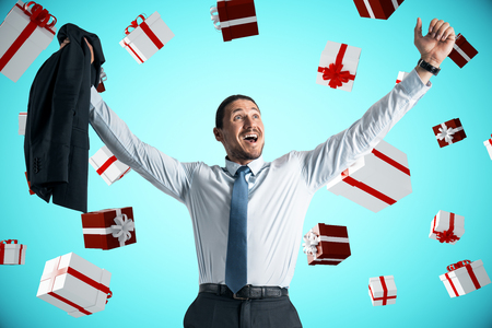Attractive businessman celebrating a lot of presents on blue background. Christmas and joy concept