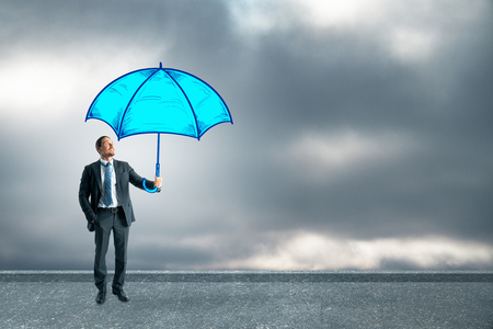 Young businessman holding drawn blue umbrella on cloudy sky background. Protection concept 스톡 콘텐츠