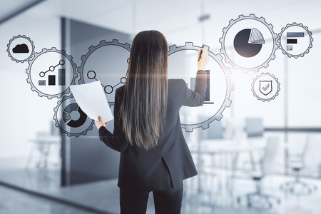 Attractive young european businesswoman using digital cogwheel business interface on blurry office interior background. Future and ai concept. 版權商用圖片