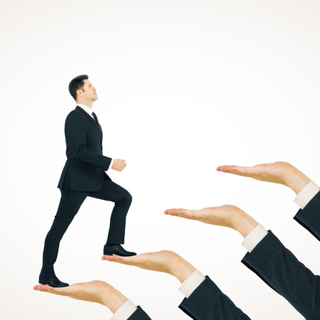 Businessman climbing hand ladder on white background. Career development and success concept