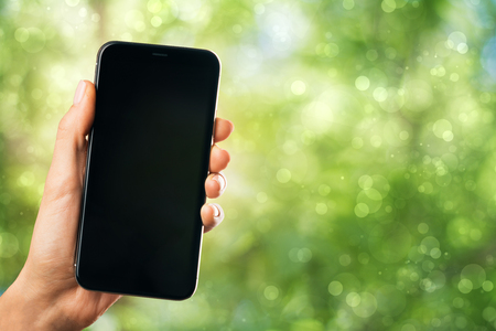 Hand holding empty mobile phone on abstract blurry green outdoor background. Device mockup concept