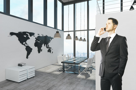 Attractive businessman talking on the phone in modern office interior. Communication, network and executives. Stock Photo