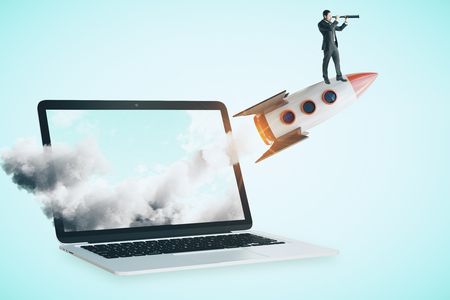 Young businessman with telescope standing on rocket launching off laptop screen. Startup and research concept.