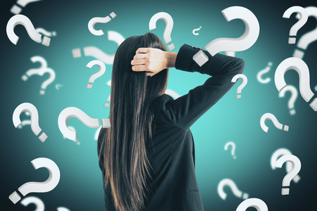 Portrait of attractive young european businesswoman with question marks. Doubt and stress concept