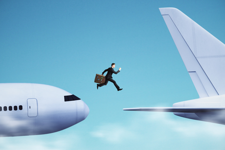 Side view of young businessman with luggage jumping from plane to plane. Challenge and traveling concept