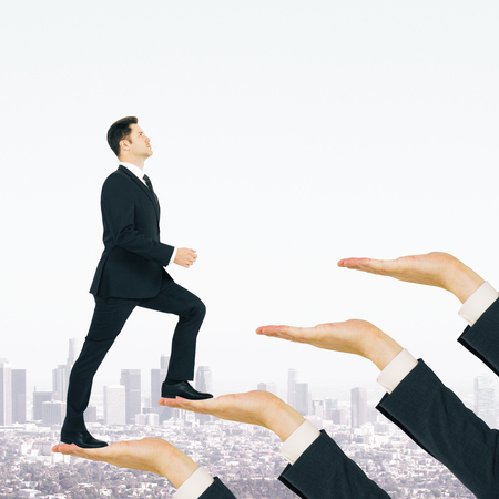 Businessman climbing hand ladder on white city background. Career development and rise concept