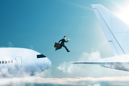 Side view of young businessman with luggage jumping from plane to plane. Challenge and risk concept