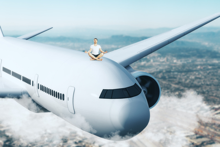 Young man meditating on airplane. Sky background. Freedom and travel concept. Stock Photo