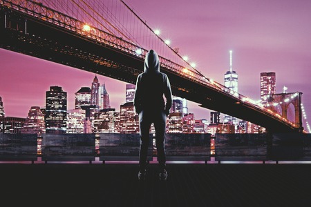 Back view of young hacker on night city background. Urban and malware concept Stock Photo