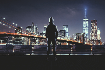 Back view of young hacker on night city background. Urban and hacking concept Stock Photo