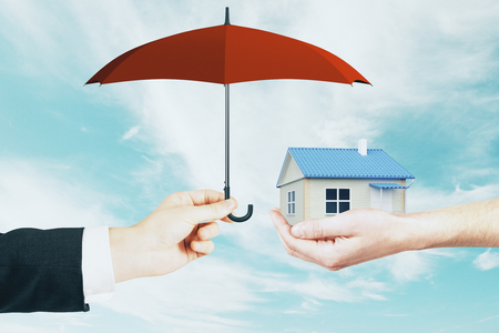 Businessman covering handed small house with umbrella on blue sky background. Mortgage and safety concept Stock fotó
