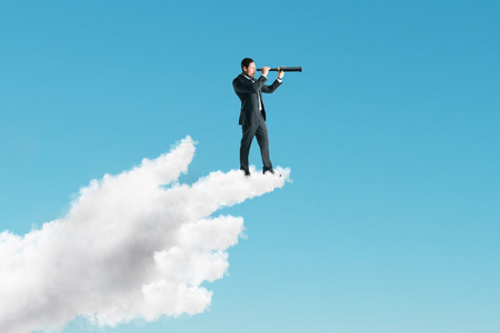 Young businessman using telescope while standing on pointing cloud hand on sky background. Vision and direction concept Stockfoto