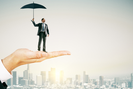 Big hand holding young businessman with umbrella on bright city background with sunlight. Protection and success concept