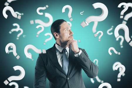 Portrait of attractive young european businessman with question marks. Doubt and confusion concept Stock Photo