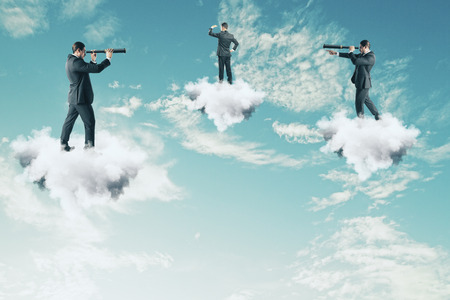 Businessmen on cloud looking into the distance with binoculars on sky background. Teamwork, vision and success concept