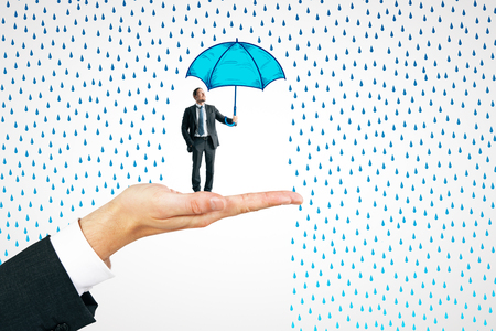 Hand holding businessman with drawn umbrella on white rain background. Protection and safety concept