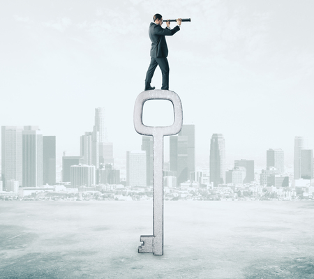 Side view of young businessman with telescope standing on big key. City background. Access and research concept
