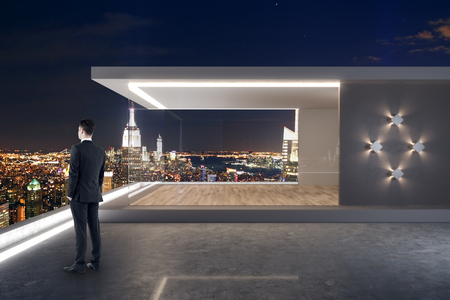 Young businessman standing on modern rooftop with penthouse and night New York city view