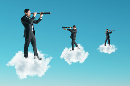 Young businessman using telescope while standing on cloud on sky background. Vision and research concept