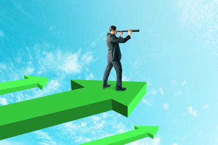 Young businessman looking into the distance while standing on green arrows. Sky background. Research and forward concept