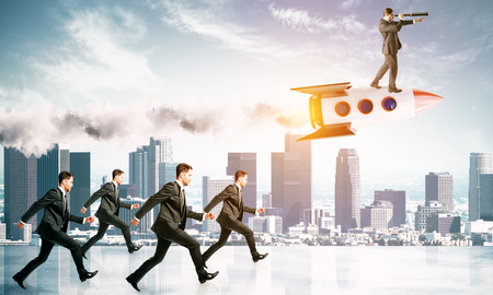 Businessmen following leader on rocket on city background. Leadership and teamwork concept Stock Photo