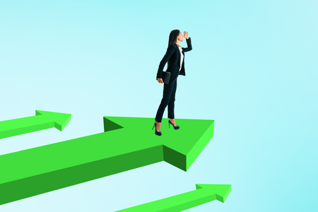 Young businesswoman looking into the distance while standing on green arrows. Sky background. Research and growth concept