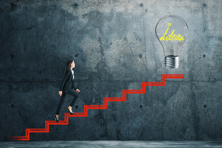 Side view of young businesswoman climbing abstract drawn stairs with idea lamp on concrete background. Ascend and innovation concept