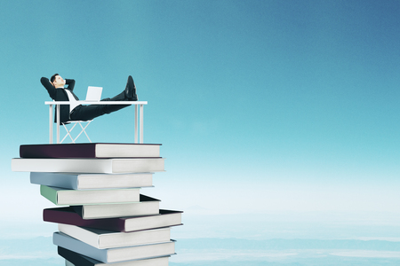 Relaxing businessman at desk placed on pile of books on sky background. Success and education concept