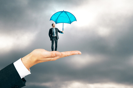 Hand holding businessman with drawn umbrella on cloudy sky background. Protection and safety concept 스톡 콘텐츠