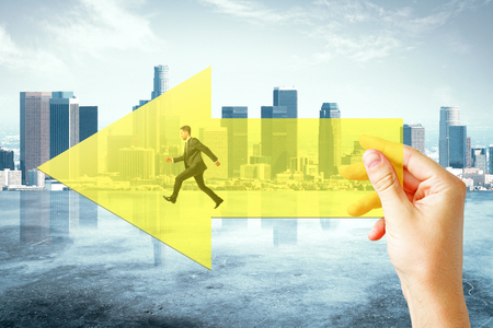 Hand holding yellow arrow with running businessman on city background. Growth and forward concept