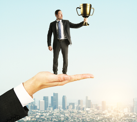 Hand holding businessman with golden cup on sky background. Leadership and success concept