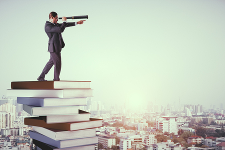 Side view of young businessman with binoculars standing on pile of books. Vision and knowledge concept