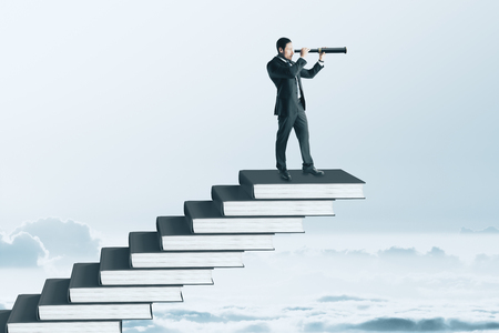 Businessman with binoculars standing on top of book pile ladder. Sky background. Education and future concept Banco de Imagens - 114608807