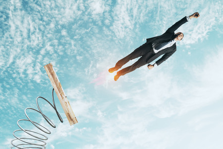 Businessman lauching off big spring on sky background with clouds. Startup and success concept