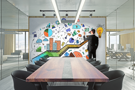 Businessman in modern meeting room with creative business sketch on whiteboard. Marketing and presentation concept. Standard-Bild - 114608728