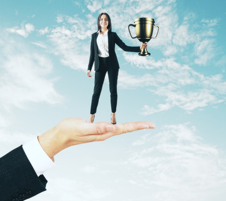 Hand holding businesswoman with golden cup on sky background. Leadership and win concept