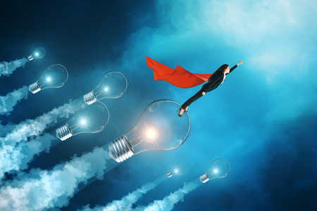 Young superhero businesswoman with cap flying with lamps on blue sky background. Leadership and innovation concept. Zdjęcie Seryjne