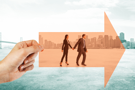 Hand holding arrow with walking businessman and woman couple on city background. Growth and teamwork concept