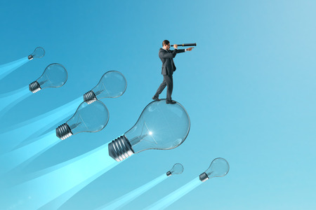 Businessman looking into thr distance on while flying on lamps on blue sky background. Idea and vision concept.