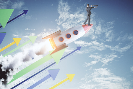 Side view of young businessman with telescope standing on launchging rocket on sky background with colorful arrows. Startup, growth and vision concept.