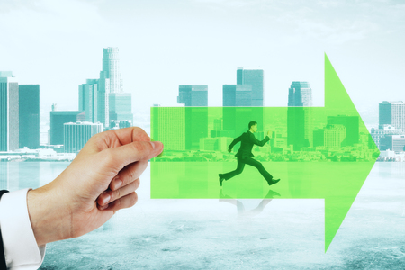 Hand holding green arrow with running businessman on city background. Growth and forward concept