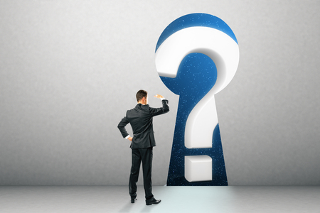 Businessman looking at question mark through key hole in wall. Confusion and access concept Stock Photo