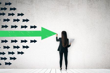Rückansicht der Geschäftsfrau, die Pfeile an der Wand zeichnet. Führungs- und Erfolgskonzept