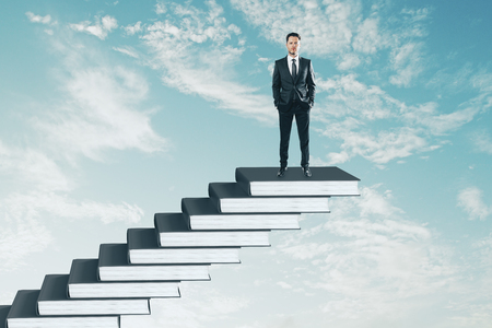 Businessman on top of book pile ladder. Sky background. Education and growth concept Banco de Imagens - 115434246