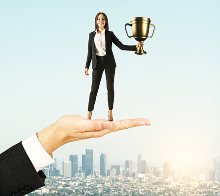Hand holding businesswoman with golden cup on sky background. Leadership and success concept