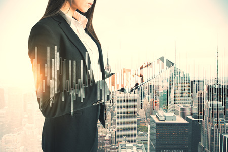 Attractive young businesswoman using tablet on abstract city background with forex chart. Trade and communication concept. Double exposure